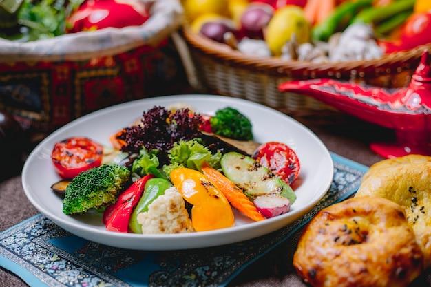 Vista lateral de ensalada de verduras a la plancha con tomate, brócoli, aguacate, pimientos y coliflor en un tazón