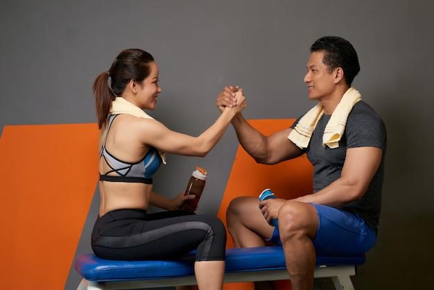 Vista lateral del entrenador físico y el cliente apoyándose mutuamente con un gesto de unidad