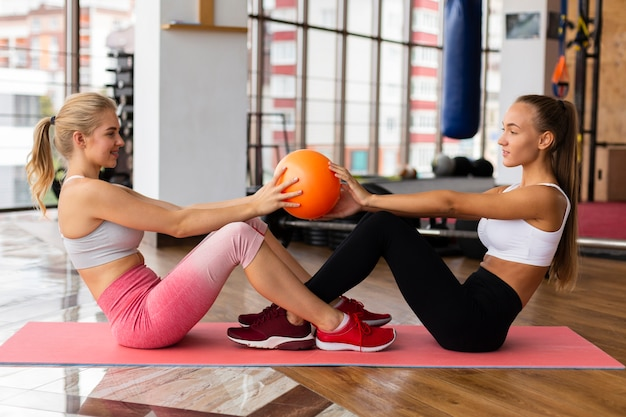 Vista lateral del entrenamiento de la mujer en el gimnasio