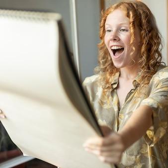 Vista lateral entusiasta mujer mirando cuaderno de bocetos