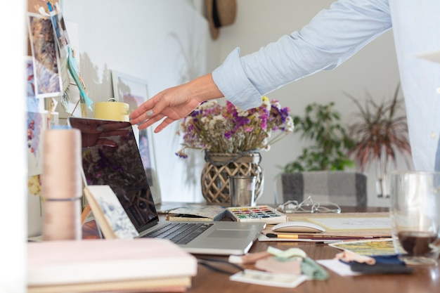 Vista lateral del escritorio con laptop y flores.