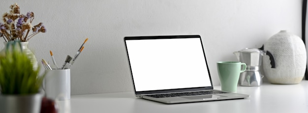 Vista lateral del escritorio de oficina moderno con pantalla en blanco portátil, herramientas de pintura y decoraciones
