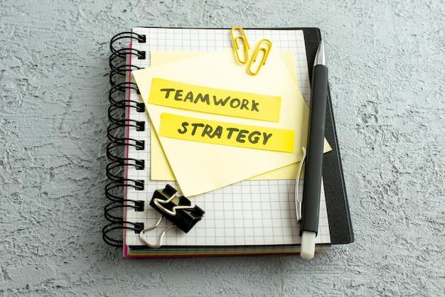 Vista lateral de los escritos de estrategia de trabajo en equipo en sobres de colores, bolígrafo en cuaderno espiral y libro sobre fondo de arena gris Foto gratis