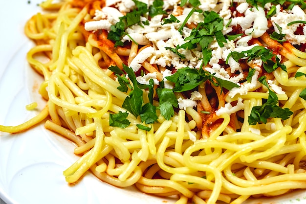 Vista lateral espaguetis a la boloñesa con carne molida salsa de tomate queso blanco y verduras en un plato