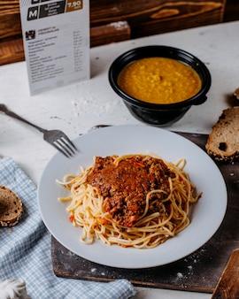 Vista lateral de espaguetis a la boloñesa en plato blanco