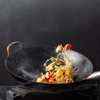 Vista lateral de espaguetis en sartén sobre fondo negro.