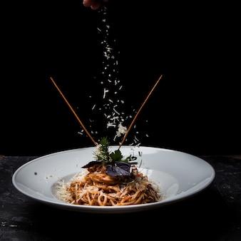 Vista lateral de espaguetis con verduras y queso ricotta en plato blanco redondo
