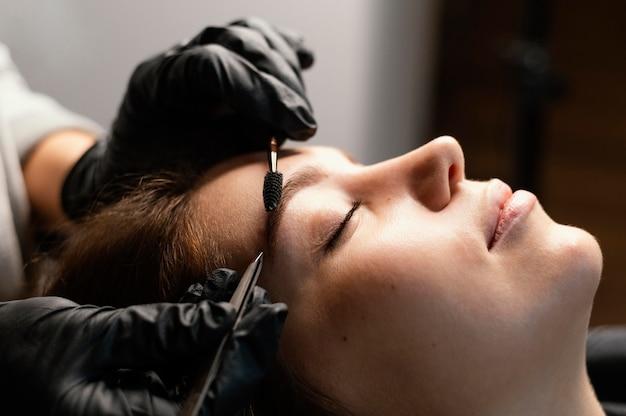 Vista lateral de la especialista femenina haciendo un tratamiento de cejas para mujer