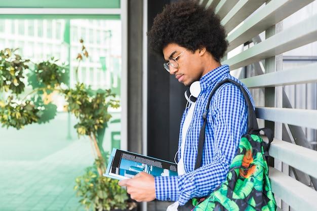 Vista lateral de un estudiante masculino adolescente que lleva el bolso en su hombro que se inclina contra la pared que lee el libro