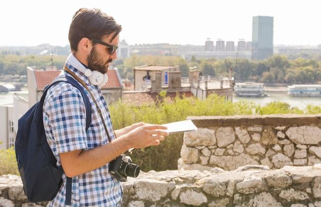 Vista lateral de un excursionista hombre mirando el mapa