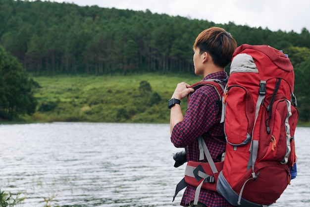 Vista lateral del excursionista con mochila grande mirando al lago alejado de la cámara