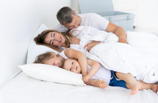 Vista lateral familia feliz tendido en la cama