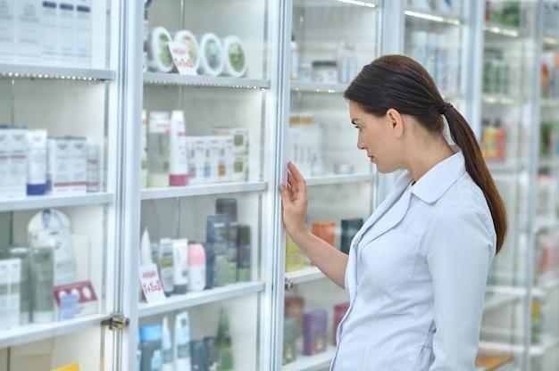 Vista lateral de un farmacéutico serio con una túnica blanca de pie ante la vitrina de la farmacia