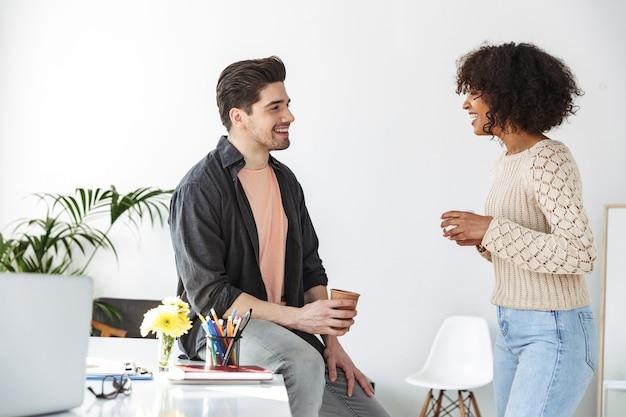 Vista lateral de felices jóvenes colegas hablando y mirando el uno al otro mientras están en la oficina