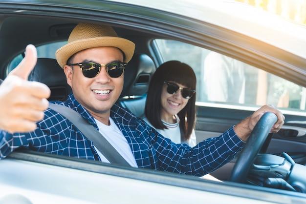 Vista lateral felicidad joven pareja asiática sentado en coche mostrar pulgar.