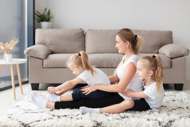 Vista lateral de la feliz familia de madre e hijas en casa