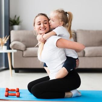 Vista lateral de la feliz madre e hija posando mientras trabaja