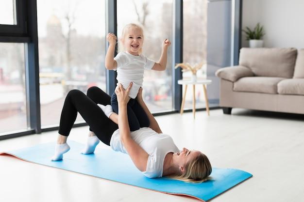 Vista lateral de la feliz madre y el niño haciendo ejercicio en casa