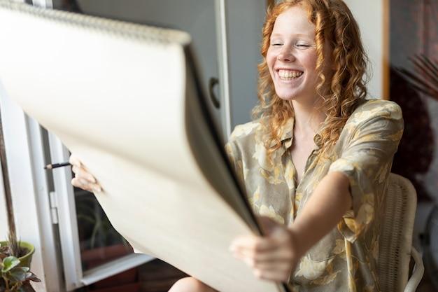 Vista lateral feliz mujer mirando cuaderno de bocetos