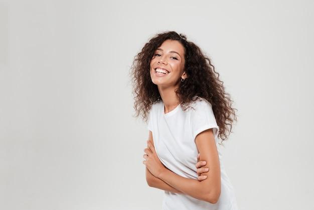 Vista lateral de feliz mujer rizada con brazos cruzados
