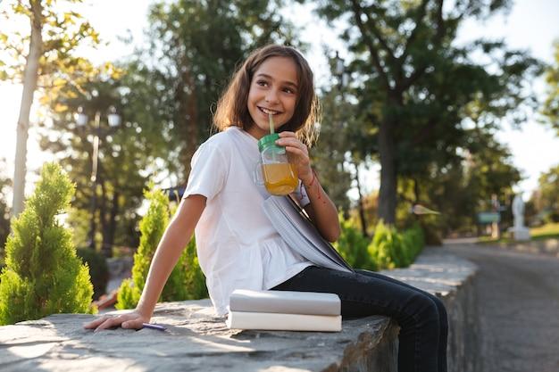 Vista lateral de la feliz niña morena sentada al aire libre