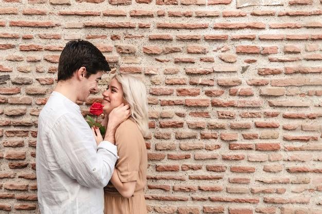 Vista lateral de la feliz pareja con rose