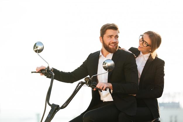 Vista lateral de la feliz pareja en trajes paseos en moto