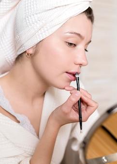 Vista lateral femenina aplicar lápiz labial