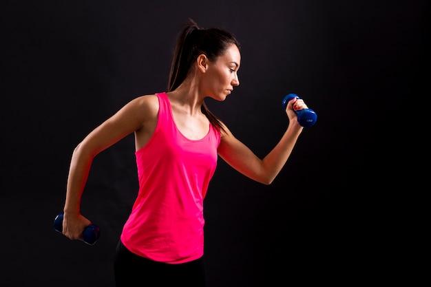 Vista lateral femenina haciendo ejercicio con pesas