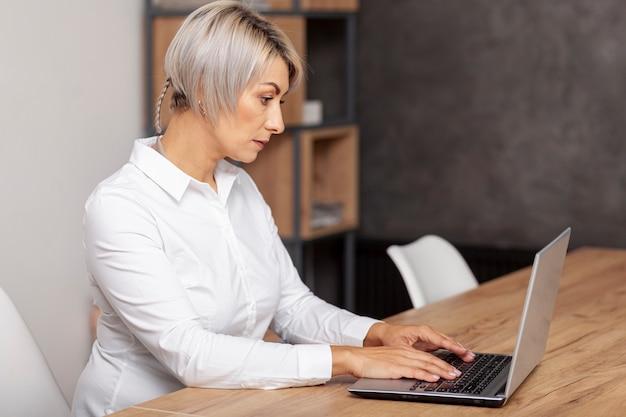 Vista lateral femenina trabajando en la computadora portátil