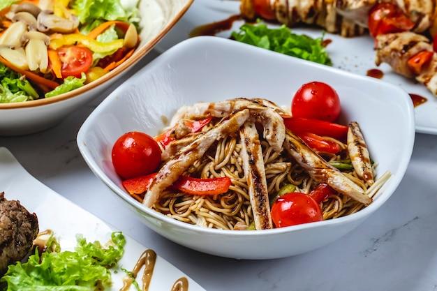 Vista lateral fideos fritos con salsa pimiento pollo a la parrilla y tomate en un plato
