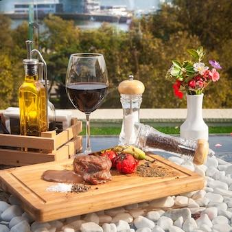Vista lateral de filete de carne con pomato sobre tabla de madera con copa de vino en la mesa de cristal con vista al mar
