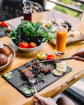 Vista lateral de filete de carne roja a la parrilla, tomate, pepino y limón en un tablero