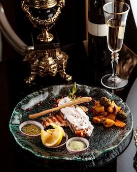 Vista lateral del filete de pescado al horno adornado con verduras especias y salsa en un plato con una copa de vino blanco sobre la mesa