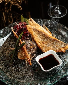 Vista lateral del filete de pescado al horno con cebolla roja y narsharab en un plato