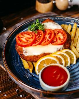 Vista lateral del filete de pollo empanizado frito con queso servido con rodajas de tomate, limones, salsa de tomate y papas fritas en rústica