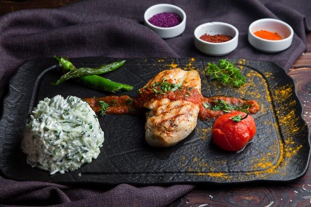 Vista lateral de filete de pollo a la parrilla con guarnición, tomate, pimiento una mesa de madera oscura horizontal
