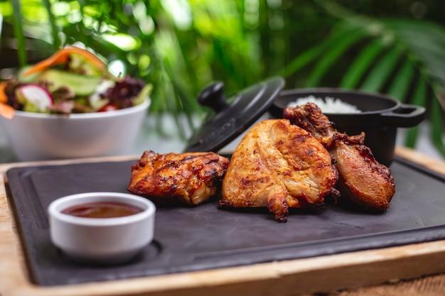 Vista lateral de filete de pollo a la parrilla con salsa y guarnición de arroz en una bandeja