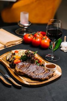 Vista lateral de filete con verduras a la plancha con salsa y una copa de vino tinto