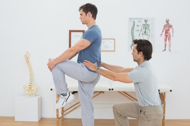 La vista lateral de un fisioterapeuta masculino que examina sirve detrás