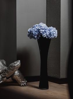 Vista lateral del florero alto de vidrio negro con flores azules en un piso de madera