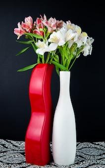 Vista lateral de flores de alstroemeria de color blanco y rosa en jarrones blancos y rojos sobre fondo negro