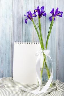 Vista lateral de flores de iris de color púrpura oscuro en una botella de vidrio con un cuaderno de bocetos sobre fondo de madera