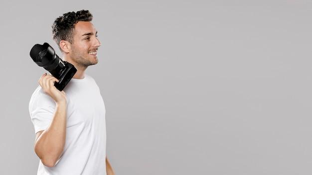Vista lateral del fotógrafo masculino sonriente con espacio de copia