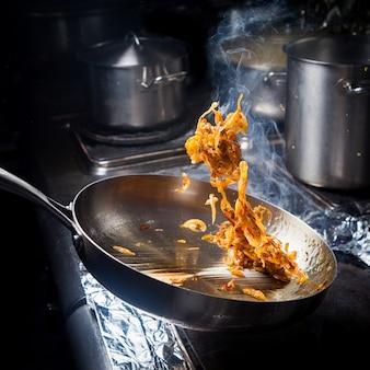 Vista lateral freír cebollas con sartén en estufa2