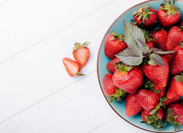 Vista lateral de fresa fresca a la derecha con albahaca y copia espacio sobre fondo blanco.