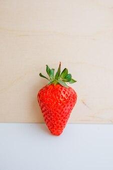 Vista lateral de fresa fresca en pared de madera clara y blanco