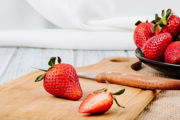 Vista lateral fresa fresca en un plato cuchillo y placa sobre fondo blanco.