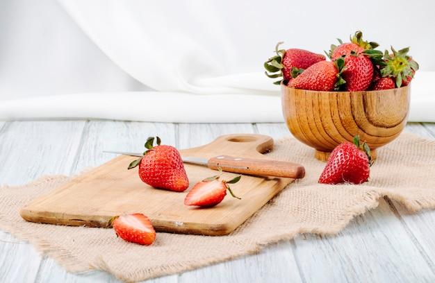 Vista lateral fresa fresca en un tazón de madera cuchillo y placa sobre fondo blanco.