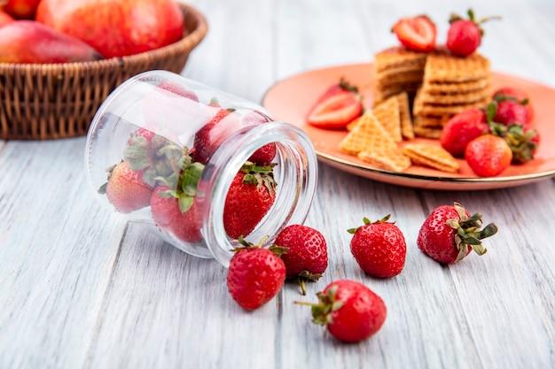 Vista lateral de fresas derramándose de tarro y tarta de fresa en placa con frutas sobre madera